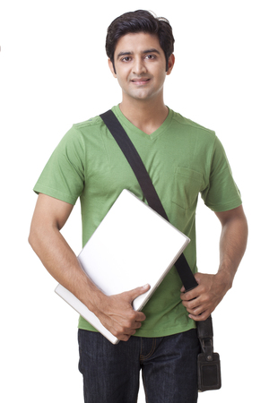 Portrait of happy young male student holding laptop