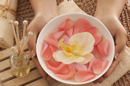 woman in bath: Rose petals and orchid in a bowl with reed diffuser