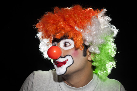 Close-up of serious male clown over white background Stock Photo