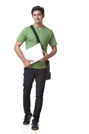 full length of college student with laptop walking over white background Stock Photo