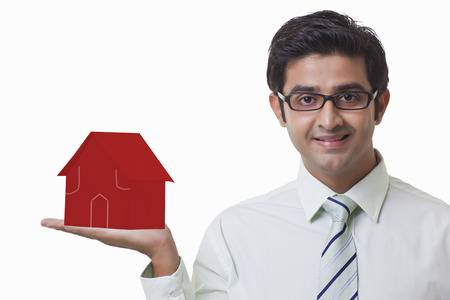 Portrait of young business man holding house model Stock Photo