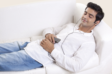 Smart young guy lying on sofa while listening to music