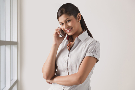 welldressed: Portrait of cute young business woman on phone call at officePortrait of cute young business woman on phone call at office Stock Photo