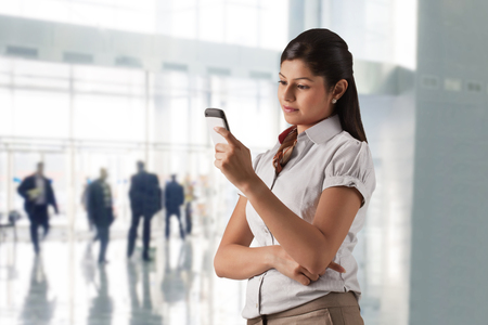 welldressed: Confident businesswoman text messaging at office Stock Photo