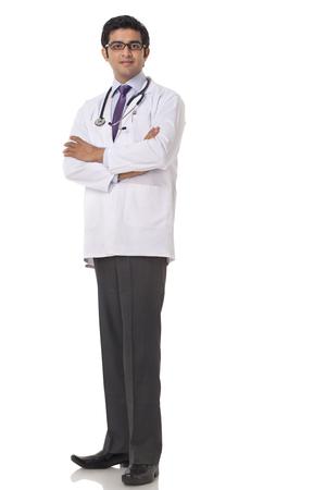 Full length of confident doctor standing over white background