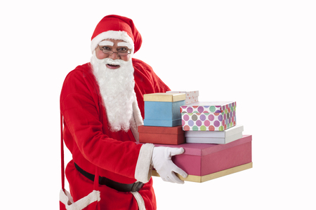 Portrait of smiling Santa Claus carrying Christmas present Stock Photo