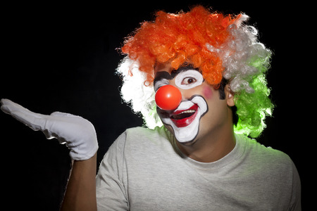 comedian: Portrait of male clown gesturing on black background Stock Photo