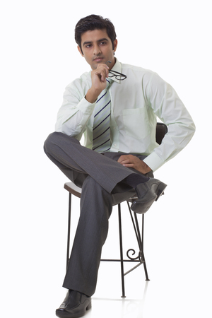 to contemplate: Handsome young executive sitting on chair and looking away
