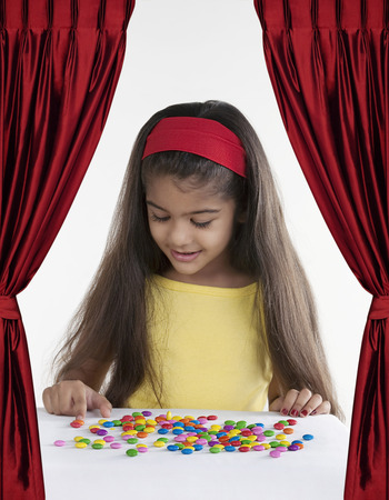 joyfulness: Girl with different coloured sweets