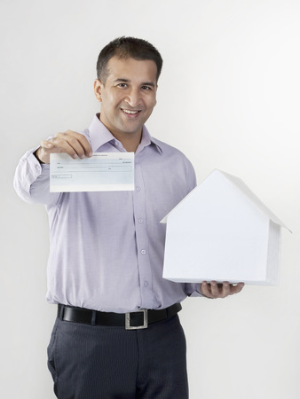 replica: Man holding a house model and cheque