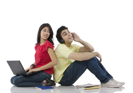 making music: Girl sitting with a laptop while boy listens to music