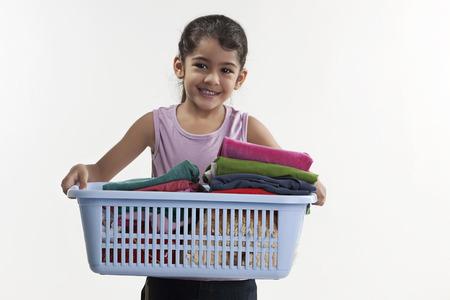 Girl carrying laundry basket Фото со стока