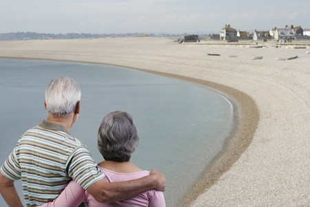 55 years old: Couple standing with their arms around each other Stock Photo