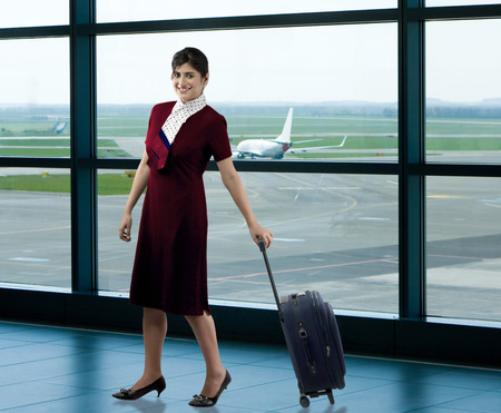 go inside: Air hostess with luggage Stock Photo