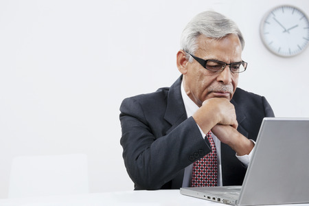 Old businessman looking at a laptop