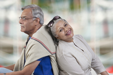 Old couple sitting back to back Stock Photo