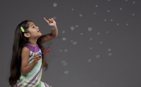 Girl trying to touch a bubble