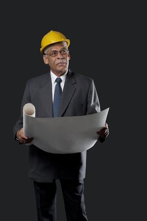 Senior engineer holding blueprints