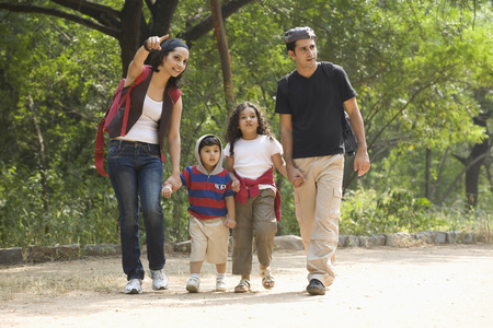 joyfulness: Family going for a walk in a park Stock Photo