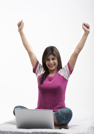 Woman with a laptop rejoicing