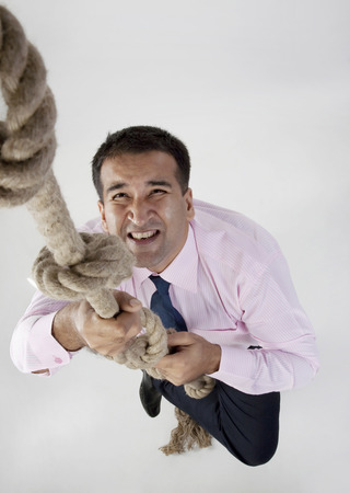 Businessman trying to climb a rope