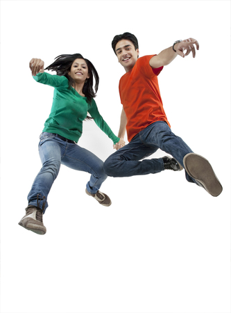 Boy and girl jumping in the air Stock Photo