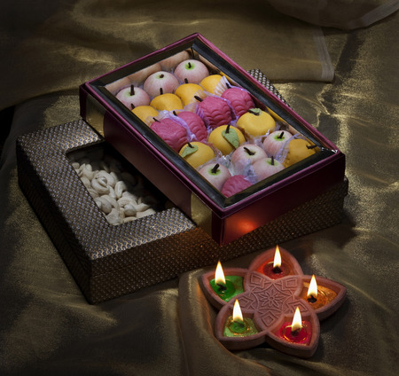 Box of sweets and nuts with diyas Stock Photo