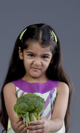 unsatisfied: Girl holding broccoli