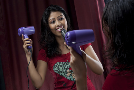 pretending: Woman singing while drying her hair Stock Photo