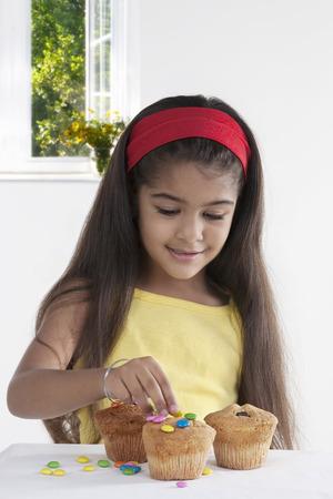 joyfulness: Girl decorating muffins Stock Photo