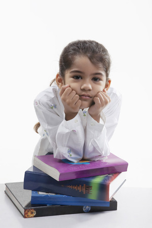 gloom: Girl leaning on a stack of books Stock Photo