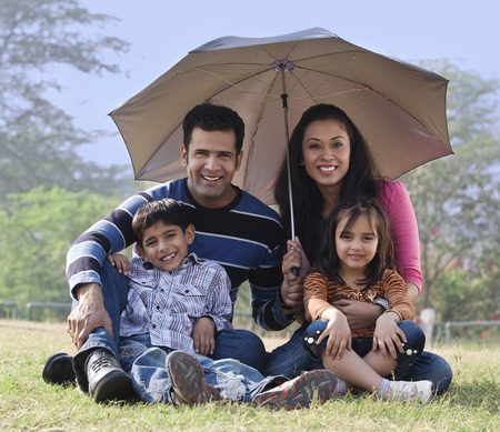Family posing with an umbrella Stock Photo