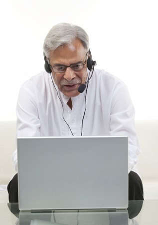 55 years old: Old man with a laptop Stock Photo