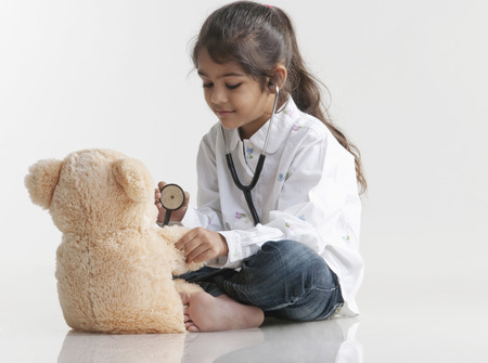 pretend: Girl playing doctor with teddy bear