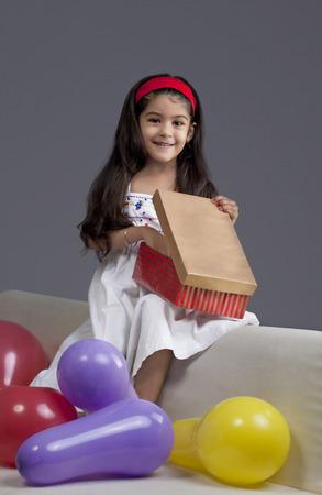 joyfulness: Girl opening gifts Stock Photo
