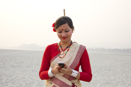 Bihu woman reading an sms on a mobile phone Stock Photo