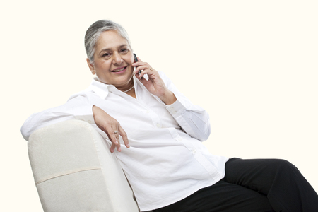 Portrait of an old woman talking on a mobile phone