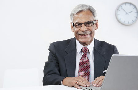 Old businessman with a laptop Stock Photo