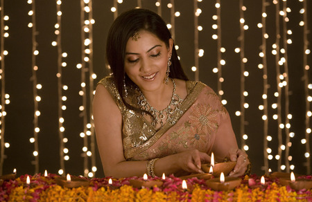 Woman lighting diyas Stock Photo