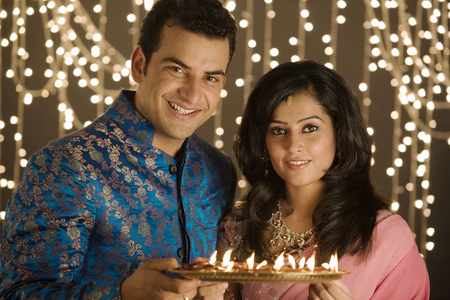 Couple holding a tray of diyas