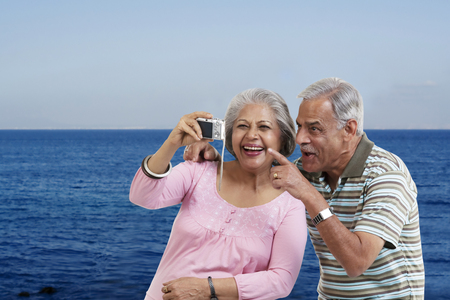 Couple looking at photographs in a camera Stock Photo