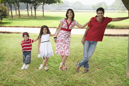 joyfulness: Family posing in a park Stock Photo