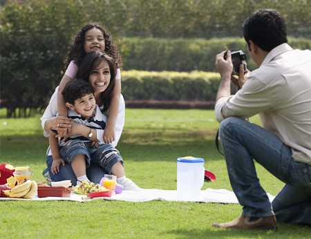 Man taking a photograph of his family Stock Photo