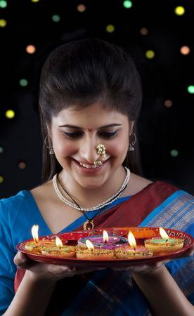 marathi: Maharashtrian woman holding a tray of diyas