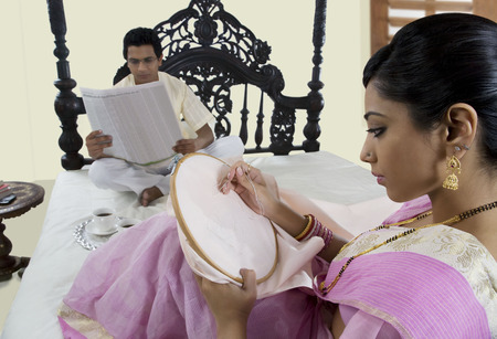 sutra: Bengali woman stitching while husband reads newspaper