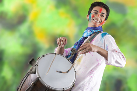 Man playing on a dhol Imagens