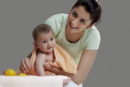 front house: Mother wiping her baby after a bath