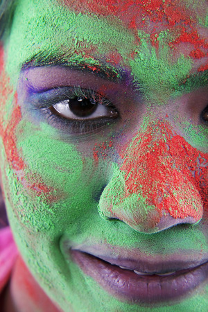 Womans face covered in holi colours Imagens