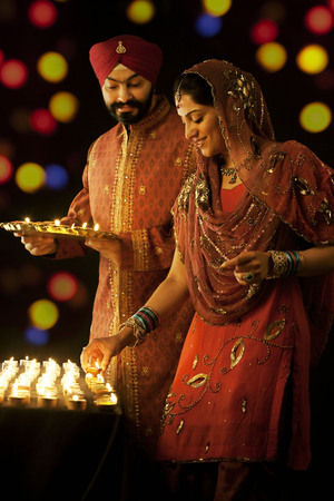 down lights: Sikh man holding a tray of diyas while the woman places them on a table