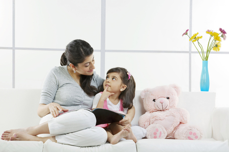 25 30: Mother and daughter sitting with a magazine